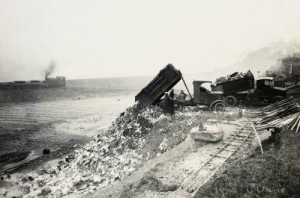 Photograph of a lorry reversing and dumping waste off the shore at Otterspool